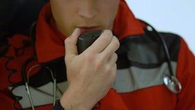 Samiec lekarka odpowiada radiem w karetce, naglący wezwanie wypadek samochodowy, zbliżenie zbiory wideo