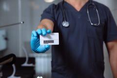 Samiec lekarka pokazuje odwiedzać karciany i patrzeć kamerę fotografia stock