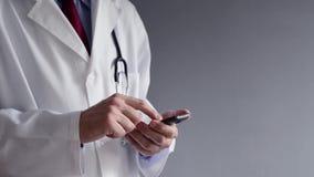 Samiec lekarka w białym żakiecie używa nowożytnego smartphone przyrząd zdjęcie wideo
