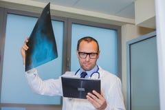 Samiec lekarka w mundurze z pastylką komputerową patrzejący promieniowanie rentgenowskie Zdjęcie Stock