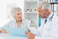 Samiec lekarka z żeńskimi cierpliwymi czytanie raportami Zdjęcia Stock