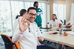 Samiec lekarka z kolegami w tle, doktorska patrzeje kamera obraz stock