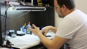 Samiec mistrz wkłada baterię i uzupełniający gromadzić telefon komórkowego zdjęcie wideo