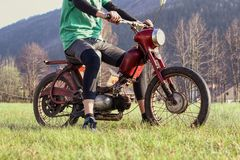 Samiec model siedzi na weterana motocyklu Jawy 50 pionierze Rewolucjonistka odnawi?cy motocykl m?od? odpowiedni? ch?opiec Czecha  zdjęcia royalty free
