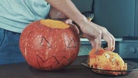 Samiec ręki łyżkuje out ziarna i zawartość bania Halloweenowy temat, dźwigarka lampion Środka strzał 4k zbiory wideo
