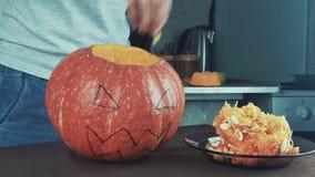 Samiec ręki łyżkuje out ziarna i zawartość bania Halloweenowy temat, dźwigarka lampion Środka strzał 4k zbiory
