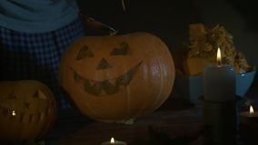 Samiec ręki łyżkuje out ziarna i zawartość bania na drewnianym stole z świeczkami przy nocą Halloweenowy temat, dźwigarka zdjęcie wideo