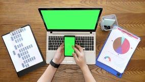 Samiec ręki scrolling telefonu pokazu z zieleń ekranem także i dotyka obok laptopu z chroma zbiory wideo