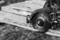 Samiec ręki z kurendą zobaczyli podczas gdy workimg z drewnem w czarny i biały Obrazy Royalty Free