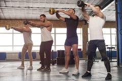 Samiec Skupiający się przyjaciele Podnosi Kettlebells Podczas trening sesji w Gym obrazy royalty free