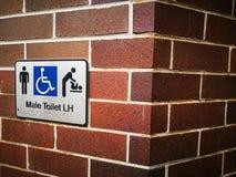Samiec toalety Dostępny L-H & dziecko zmiana, Niepełnosprawny Dostępny znak na czerwonym ściana z cegieł fotografia royalty free