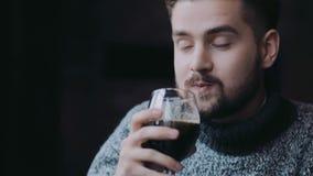 Samiec trzyma butelki piwo, kubek piwo i piją mnie z przyjemnością, śmiają się zdziwionego z rezultatem i kontynuują, zbiory