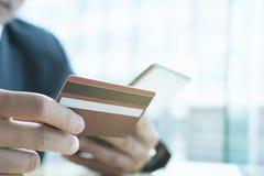Samiec trzyma kredytową kartę i używa mądrze telefon komórkowego dla onli obraz royalty free