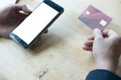 Samiec trzyma kredytową kartę i używa mądrze telefon komórkowego dla onli Obrazy Stock