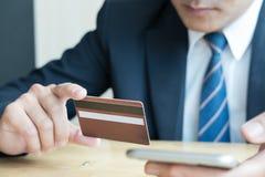 Samiec trzyma kredytową kartę i używa mądrze telefon komórkowego dla onli Obrazy Royalty Free