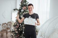 Samiec trzyma prezenta ono uśmiecha się i pudełko Święto Bożęgo Narodzenia pojęcie Przystojny mężczyzna w koszula z teraźniejszym Zdjęcie Stock
