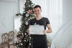 Samiec trzyma prezenta ono uśmiecha się i pudełko Święto Bożęgo Narodzenia pojęcie Przystojny mężczyzna w koszula z teraźniejszym Fotografia Stock