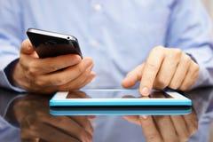 Samiec używa mądrze telefonu komórkowego i pastylki komputer przy to samo Fotografia Royalty Free