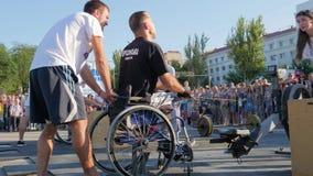 Samiec upośledzająca na koła krześle angażuje w sportach z trenerami na rynku przed ludźmi zdjęcie wideo