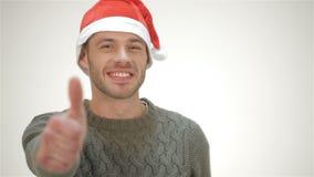 Samiec w Santa ono uśmiecha się i pokazuje kapeluszowym kciuku zdjęcie wideo