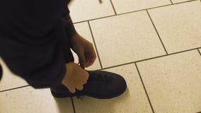 Samiec wiąże shoelaces na butach stoi na dachówkowej podłodze, wygodny obuwie, POV zbiory wideo