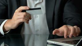 Samiec wkłada numer kartego na laptopu komputerze osobistym w kostiumu, robi zakupy online, transakcje zdjęcie wideo
