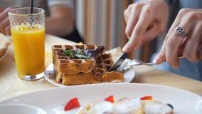 Samiec wręcza cięciom yummy belgijskich gofry z rozwidleniem w restauraci i nożem zbiory wideo