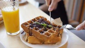 Samiec wręcza cięciom yummy belgijskich gofry z rozwidleniem w restauraci i nożem zbiory