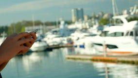 Samiec wręcza mienia smartphone na zamazanym tle port z jachtami zbiory wideo