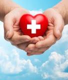 Samiec wręcza mieniu czerwonego serce z bielu krzyżem Fotografia Royalty Free
