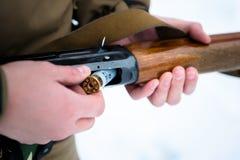 Samiec wręcza myśliwy wkładającego ładownicy 12 kaliberu karabin na backg Fotografia Royalty Free