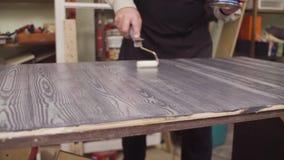 Samiec wręcza nakrycie malującą drewnianą powierzchnię z lakierem zbiory