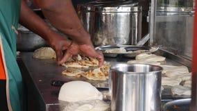 Samiec wręcza robić tradycyjnemu Indiańskiemu jedzeniu dzwoniącemu «Roti Canai « 4K zdjęcie wideo