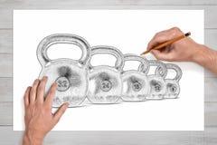 Samiec wręcza rysować kilka kettlebells różny ciężar z ołówkiem na białym papierze Fotografia Royalty Free