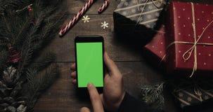 Samiec wręcza scrolling, klapanie, zbliża strony na czarnym smartphone z zieleń ekranem Chroma klucz Odgórny widok pionowo zbiory
