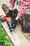 Samiec wręcza stawiającego saber saw na granitowej cegiełce Fotografia Royalty Free