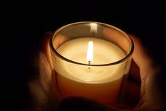 Samiec wręcza trzymać świeczkę w przejrzystym szklanym jaśnieniu w ciemności jako symbol kontemplacja, medytacja i calmness, obrazy royalty free