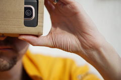 Samiec wręcza trzymać jako symbol nowożytny cyfrowy życie kartonowych gogle na twarzy Zdjęcia Royalty Free