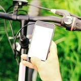 Samiec wręcza trzymać smartphone podczas gdy siedzący na rowerze górskim na lasowej drodze Pojęcie nawigacja, lato aktywny fotografia stock