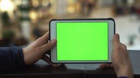 Samiec wręcza używać pastylkę z zieleń ekranem w zakupy centrum handlowym Udział ludzie przy tłem zbiory