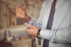 Samiec wręcza załatwiać eleganckich srebnych cufflinks na błękitnych koszulowych mankiecików rękawach w formalnym kostiumu Fotografia Royalty Free