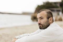 Samiec & x28; brunette& x29; z brodą w białym pulowerze patrzeje s Zdjęcia Stock