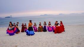 SAMIL, ESPANHA - 20 de junho de 2017: Um grupo de mulheres que dançam na praia, na hora do por do sol, em trajes aciganados fotografia de stock royalty free