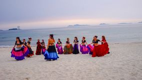 SAMIL, SPAIN - 20th JUNE, 2017: A group of women dancing on the beach, at the sunset hour, in gipsy costumes royalty free stock photography