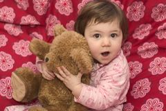 Samira Bear. Little girl in Pyjamas on the bed, holding her teddybear, making faces stock image