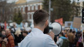 Samla folk i stad Grabben skriker in i högtalaren Folkmassan på gatan arkivfilmer