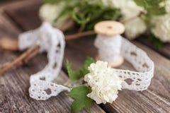 Samla ihop buketten av vita blommor med snör åt på mörker åldras riden ut träbakgrund Royaltyfri Foto