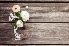 Samla ihop buketten av vita blommor med snör åt på mörker åldras riden ut träbakgrund Royaltyfri Bild