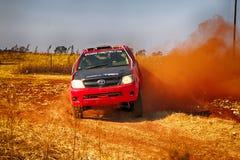 Samlar den RÖDA lastbilen för HD som upp sparkar damm på vänden ar Royaltyfria Bilder