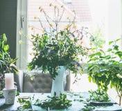 Samlar ihop lösa blommor för stor sommar i den vita vasen på tabellen i vardagsrum på fönstret Hem- livsstil royaltyfri fotografi